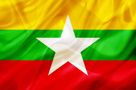 Myanmar country flag symbol on silk or silky waving texture. Smooth fabric or material