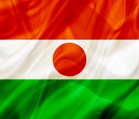 Niger country flag symbol on silk or silky waving texture. Smooth fabric or material
