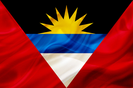 Antigua and Barbuda country flag symbol on silk or silky waving texture. Smooth fabric or material