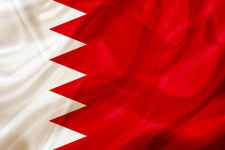 Bahrain country flag symbol on silk or silky waving texture. Smooth fabric or material