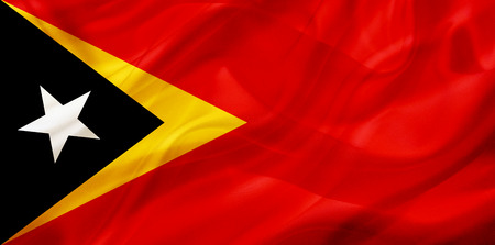 East Timor country flag symbol on silk or silky waving texture. Smooth fabric or material Stock fotó