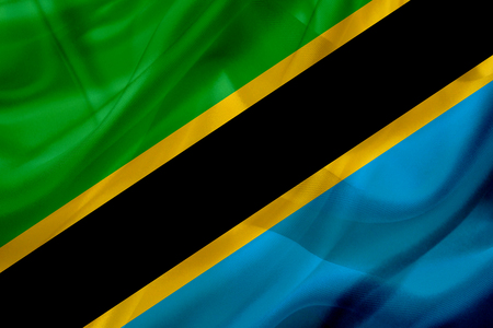 Tanzania country flag symbol on silk or silky waving texture. Smooth fabric or material Banque d'images - 123545839