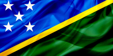 The Solomon Islands country flag symbol on silk or silky waving texture. Smooth fabric or material Banque d'images - 123545842