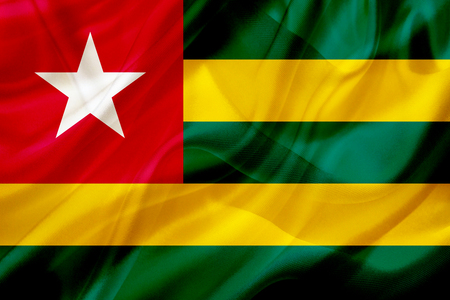 Togo country flag symbol on silk or silky waving texture. Smooth fabric or material Banque d'images - 123545844