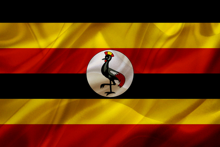 Uganda country flag symbol on silk or silky waving texture. Smooth fabric or material Banque d'images - 123545851