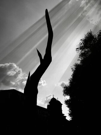 Black and white photography of a church with tree silhouette and clouds