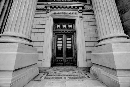 Massive and beautiful ancient roman columns with wooden door architecture wide angle photography. Black and white photo Reklamní fotografie