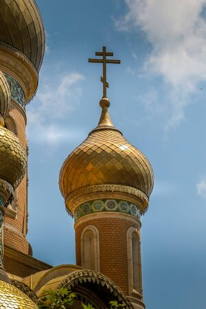 Classic Russian Christian Orthodox church golden plated close up with cross and clouds