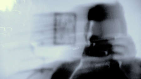 Artistic blurred photo of a photographer taking a selfie in the mirror. Abstract blur photography. Art concept