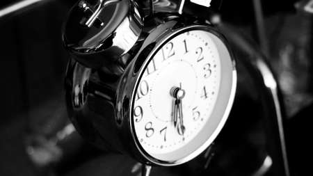 Black white big metallic clock close up. Time or showing time concept. Classic retro mechanical alarm clock with ringer. Time passing or waking up in the morning 免版税图像