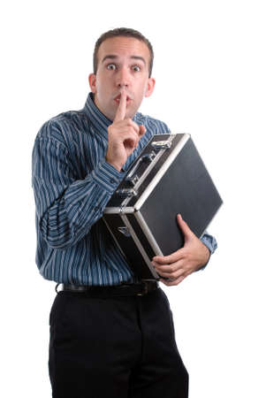 A young employee is sneaking away a case of private documents and telling the viewer to be quiet, isolated against a white background Stockfoto