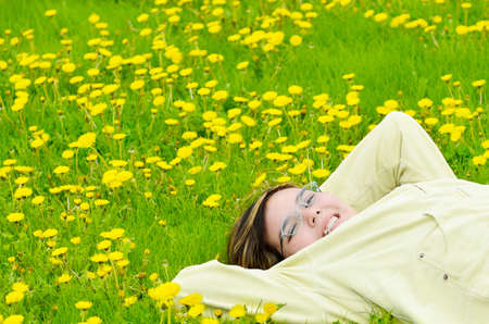 A young preteen girl is lying in the grass, relaxing in the sun. photo