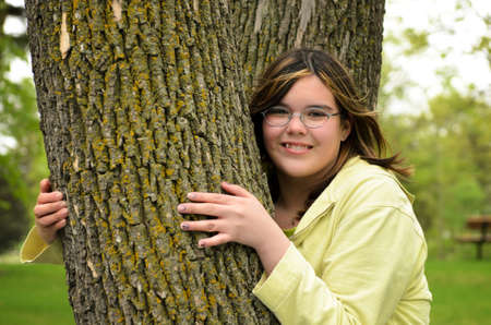 A smiling young girl is hugging a tree. photo