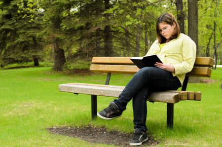 A young girl is sitting on a bench, reading a good book. photo