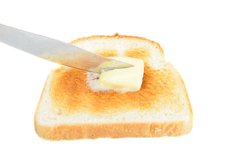 buttered: A slice of toast being buttered with a knife, isolated on white.