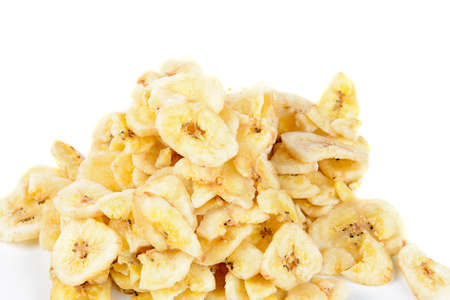 dehydrated: A pile of dried banana chips, isolated against a white background.
