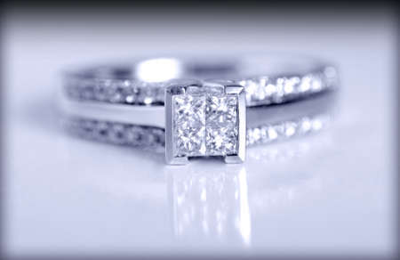 Closeup shot of a diamond engagement ring shot on a grey background.