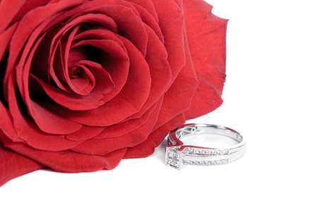 Diamond engagement ring and a red rose, isolated on a white background.
