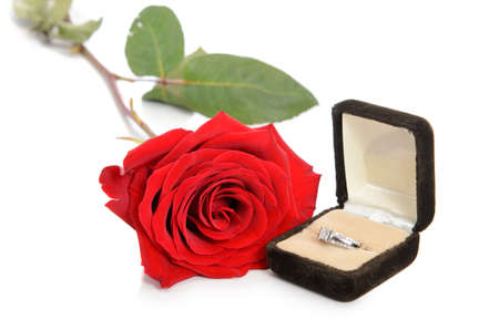 A diamond engagement ring in a jewellery box, shot next to a red rose, isolated against a white background.