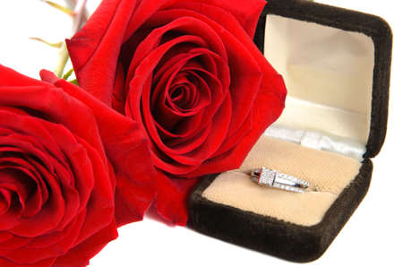 An engagement ring with red roses next to it, isolated against a white background. Stock Photo