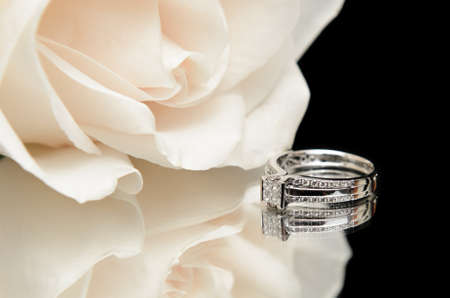 A diamond engagement ring with a white rose, shot with a reflection on a black background. Stock Photo