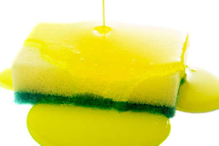 Closeup view of liquid soap being poured on a dish sponge