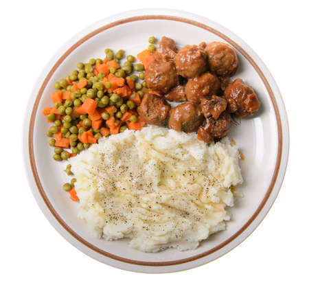 An american supper of mashed potatoes, with sweet and sour meatballs with peas and carrots. Stock Photo - 14589636
