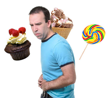 upset stomach: A man is suffering from a stomach ache from eating sweets, isolated against a white background. Stock Photo
