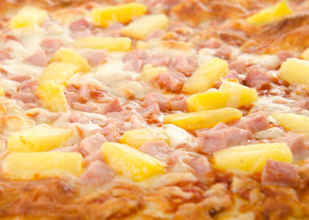 Closeup of a cooked hawaiian pizza with pineapple and ham.