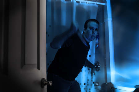 A halloween killer is sneaking around in a bathroom, about to murder someone in the shower Stock Photo - 15483945
