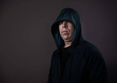 A man in his 30s wearing a hoodie shot against a grey background. Stock Photo