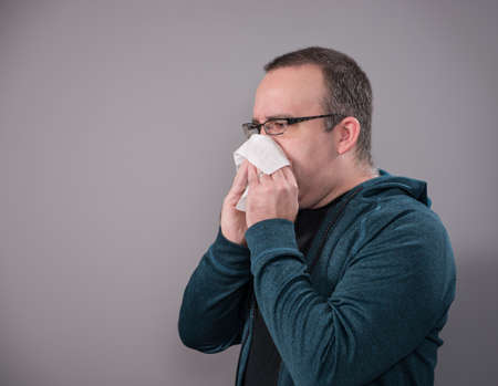 A man blowing his nose with a tissue, shot on a grey background with copyspace for your text.