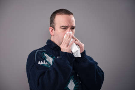 A sick man in his 30s is blowing his nose, shot against a grey background
