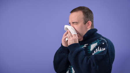 A sick man or a man with allergies is blowing his nose, with copyspace for text Stock Photo