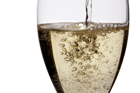 Pouring champagne into glass  isolated on white.Detail, close up.Studio shot.