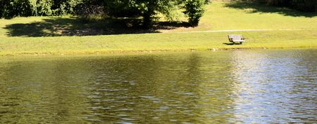 Landscape shot of single park bench next to water Stock Photo