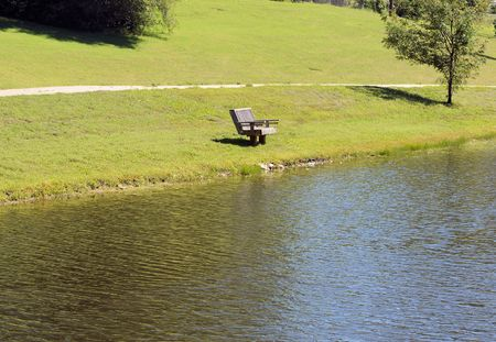 Lonely park bench next to lake Stock Photo