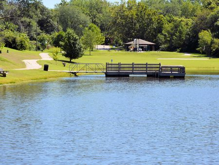 Park with fishing dock on lake Stock Photo