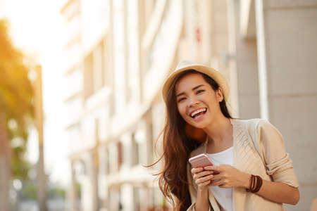 Gelukkige jonge Aziatische vrouw met smartphone permanent in de straat