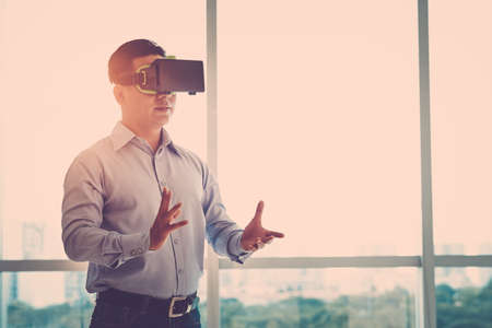 simulations: Businessman making gestures when wearing virtual reality goggles Stock Photo