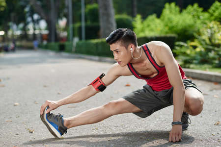 outdoor training: Asian young jogger stretching legs outdoors Stock Photo