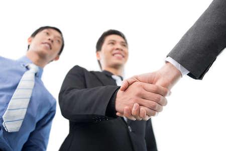 manos estrechadas: Business partners exchanging firm handshakes