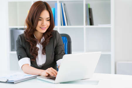 Charming young woman in formalwear computing in office Stock Photo