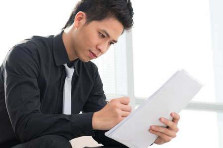 pile of documents: Young businessman reviewing a pile of documents Stock Photo