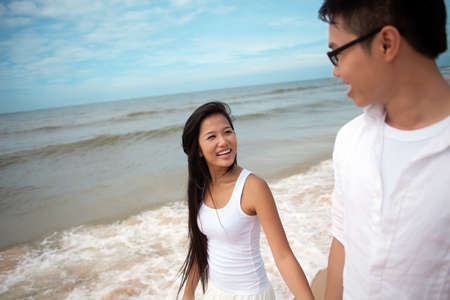 Smiling lovers walking along the beach