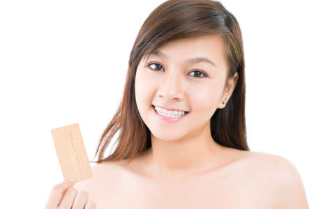 Isolated portrait of a cute girl holding a golden credit card