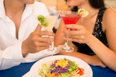 Couple clinking cocktails while having a romantic dinner