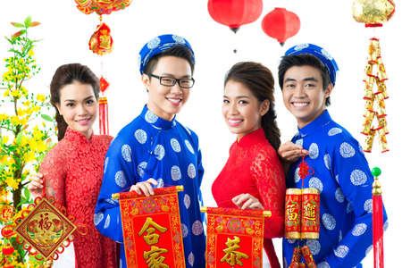 Four Vietnamese showing Tet symbols with traditional greetings