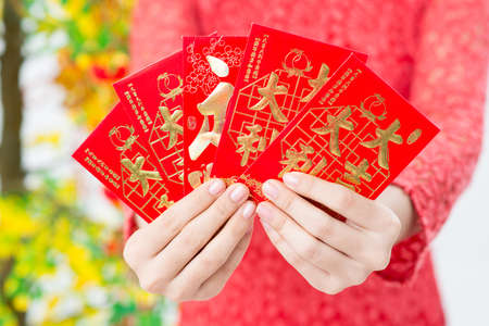 Close-up of Vietnamese red envelopes with money being presented on Tet
