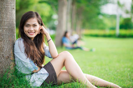 Young girl sitting at a tree and smiling at camera